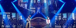 Aktor The Penthouse memakai jaket panjang dengan warna coklat, bernyanyi di acara King of Masked Singers